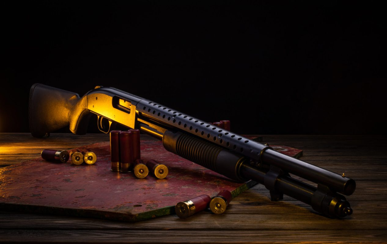 Classic pump action shotgun and cartridges for it. A 12-gauge smoothbore gun on a wooden table, illuminated with yellow light.