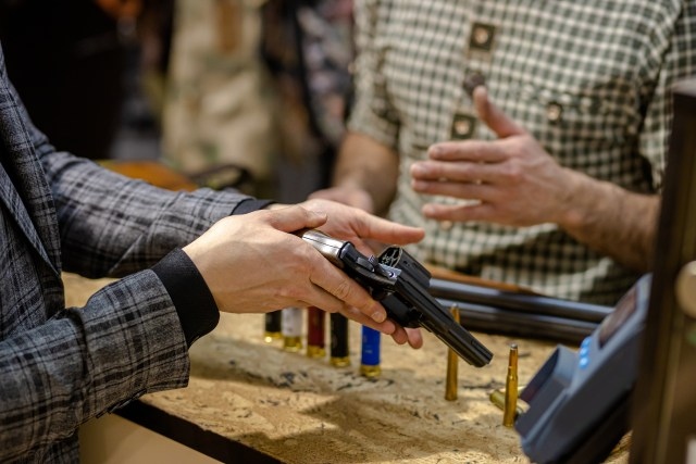 close-up photo of men using and inspecting gun in store. salesman explain how to use it, customer hold it in hands