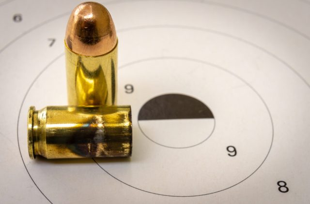 A 45 acp bullet with a paper target in the background