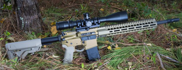 AR-15 with rifle scope built for long-range shooting that is on the forest floor
