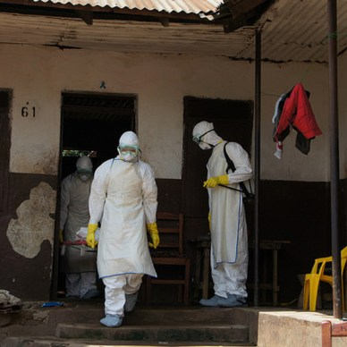 Picture shows two men in decontaminate suits carrying an Ebola patient on a stretcher