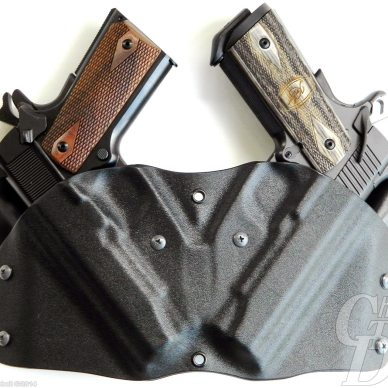Black dual holster with 2 brown gripped pistols on a white background