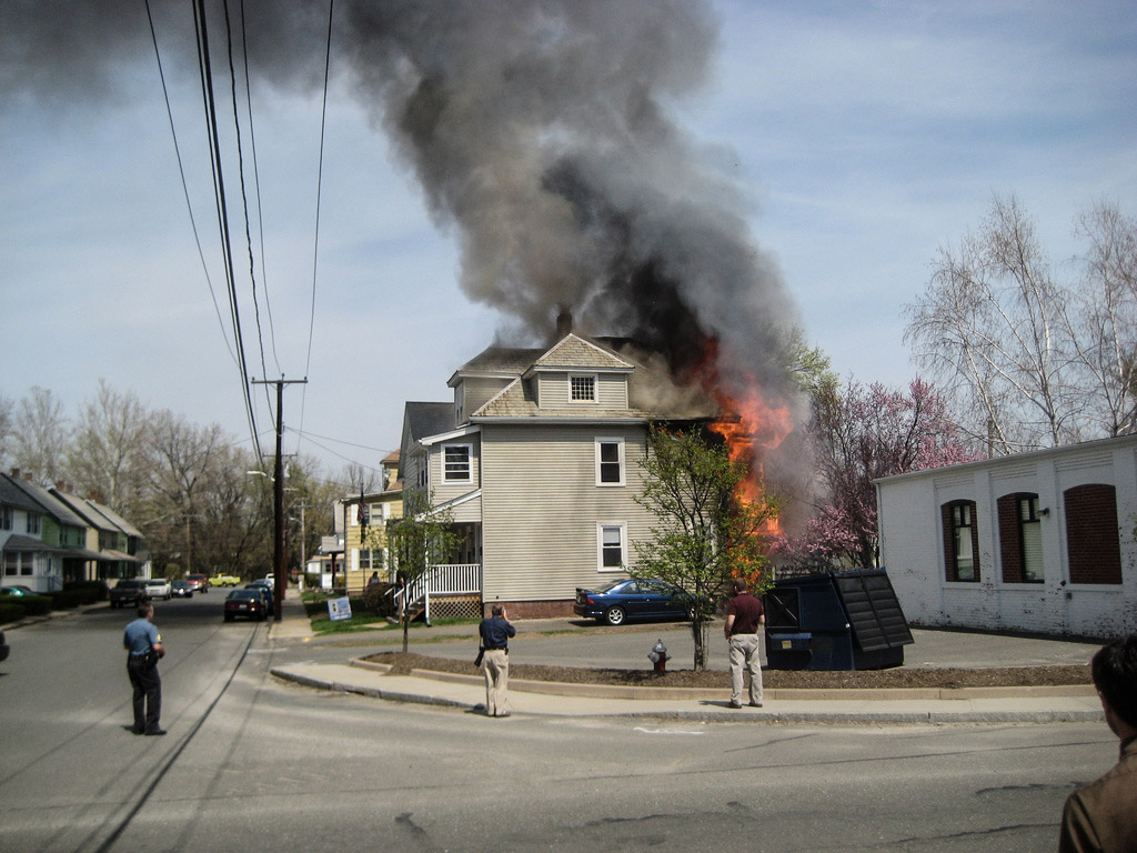 Image shows an older two-story home on fire