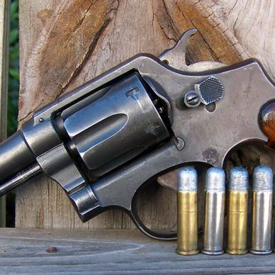 A World War 2 vintage brown-handled Smith and Wesson Victory Model with gold and silver 200 grain lead bullet handloads, sitting on a gray board and leaning against several light brown colored boards.