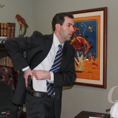Jason Hanson demonstrating drawing from concealed carry wearing a gray suit, white shirt and striped tie