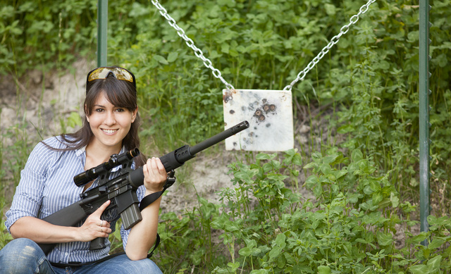 Picture shows a woman holding a black AR-15 chambered for .458 SOCOM in front of steel target.