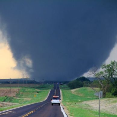 This pictures shows a large tornado in the distance.