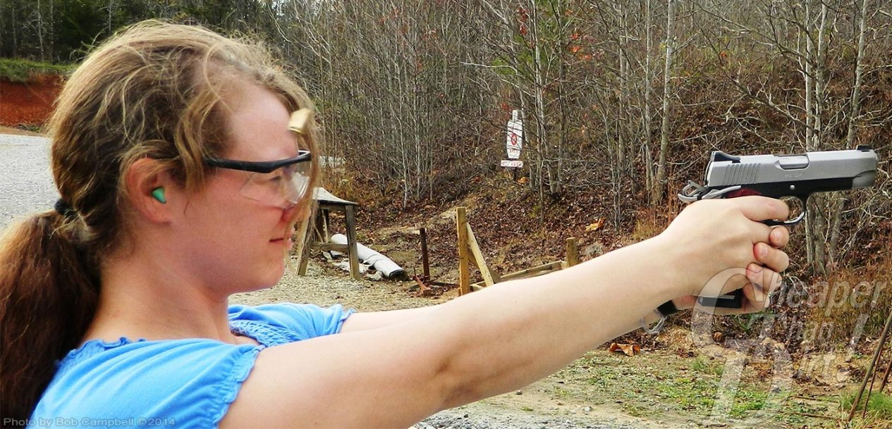 Blond woman in blue shirt shoots aluminum framed handgun