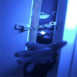 Burglar reaching through a door with a chain lock