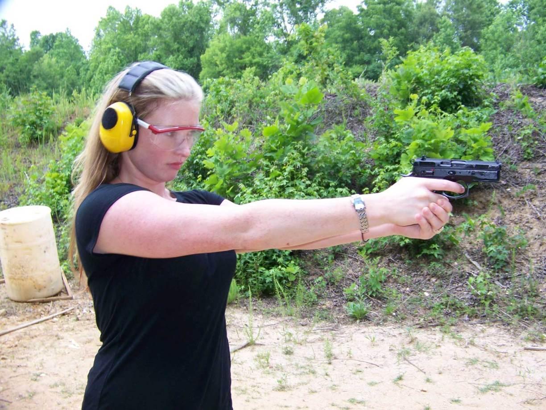 Woman shooting the CZ 9mm wearing yellow ear muffs