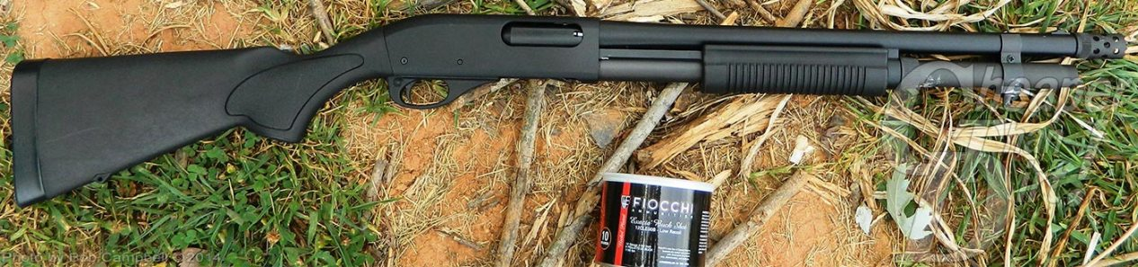 Black Remington 870 pump, barrel pointed to the right and 1 closed can of Fiocchi cartridges on the dirt.