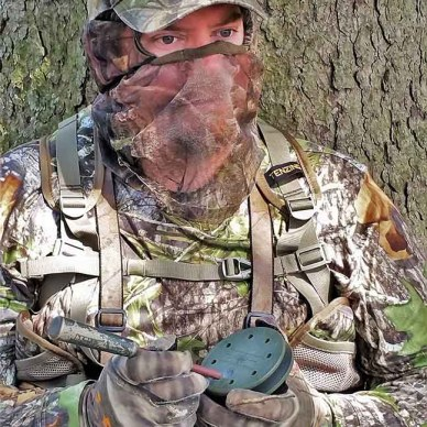 Hunter in camo using a slate call for turkeys