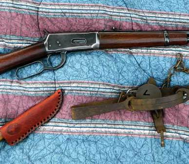 Winchester model 1894 on red and blue blanket with a knife and leg trap