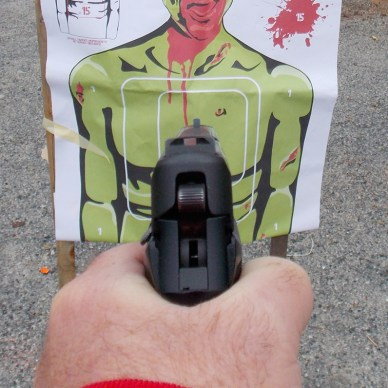 Sights of a pistol being pointed a zombie target at close range