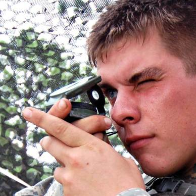 Young man in camo getting a compass reading, face pointed to the left.