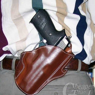 Brown DM Bullard pancake holster with black gripped handgun on the hip of a man wearing gray pants and a tan-and-gray striped shirt.