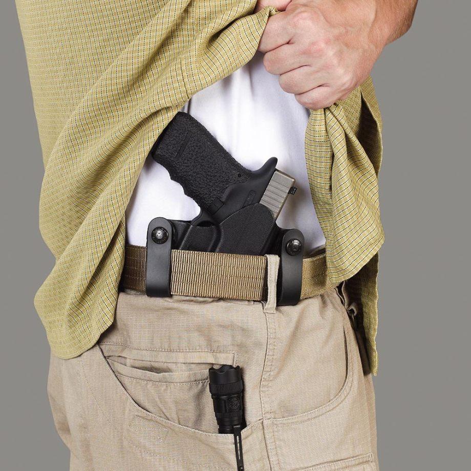 Man lifting his shirt to show a concealed handgun