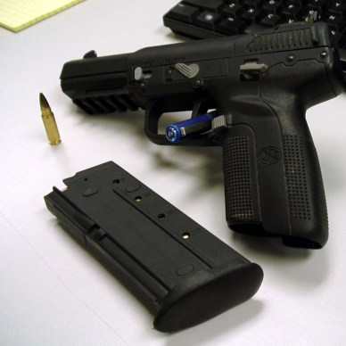 Black Five-seveN USG Pistol and black cartridge leaning against a black keyboard on a gray-to-white background