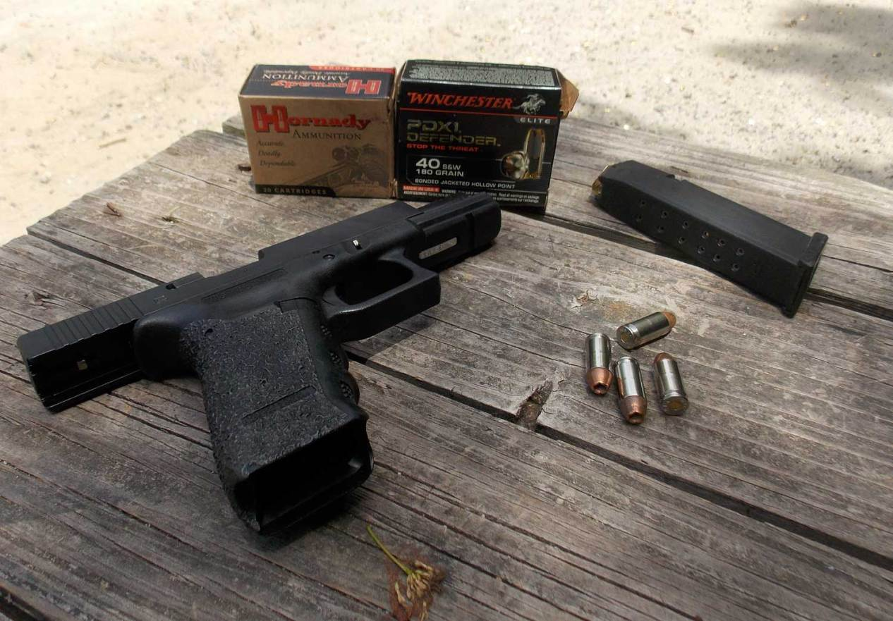 Glock 22C on picnic table with ammunition