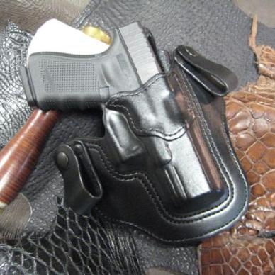 Glock 19 in black leather holster resting on swatches of exotic skins.