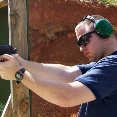 Young man in blue t-shirt, green ear protection and sunglasses practices shooting a black Beretta 9mm