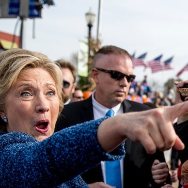 Hillary Clinton wearing a blue dress pointing into the crowd