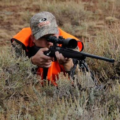 HUnter wearing blaze orange shooting a McMillan rifle from a prone position through sage brush.