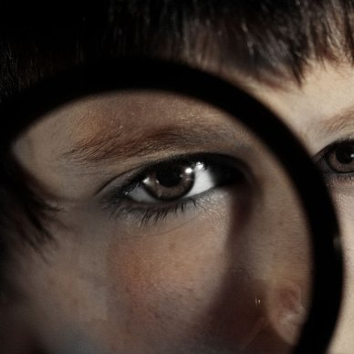 A young brown haired child holds a magnifying glass up to his eye.
