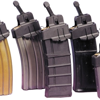 Five AR-15 magazines with a gold-toned one on the left and four others in shades of gray on a white background.