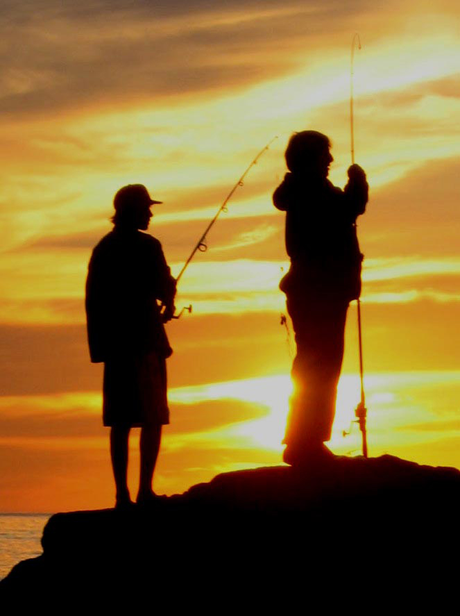 Picture shows two men holding fishing poles against an orange sunset.