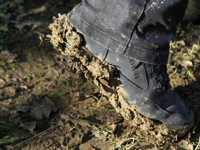 Picture shows a black boot stepping in mud
