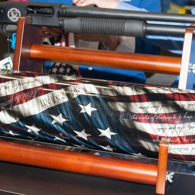 Mossberg 500 pump-action shotgun sitting on top of a carry tube decorated with the American flag.