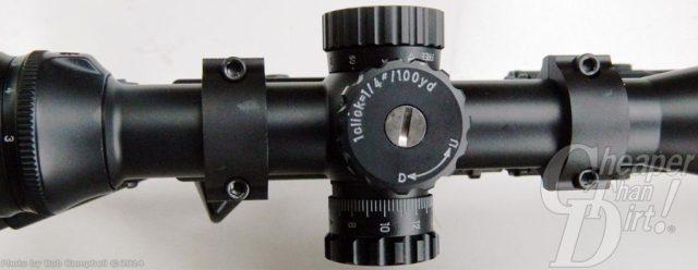 Black Nikon M223 riflescope focused on the adjustment knob on a light gray background