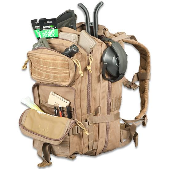 Tan ModGear Tracker Three-Day Assault Pack with tons of pockets and sample gear such as ear protection a flashlight and light sticks.