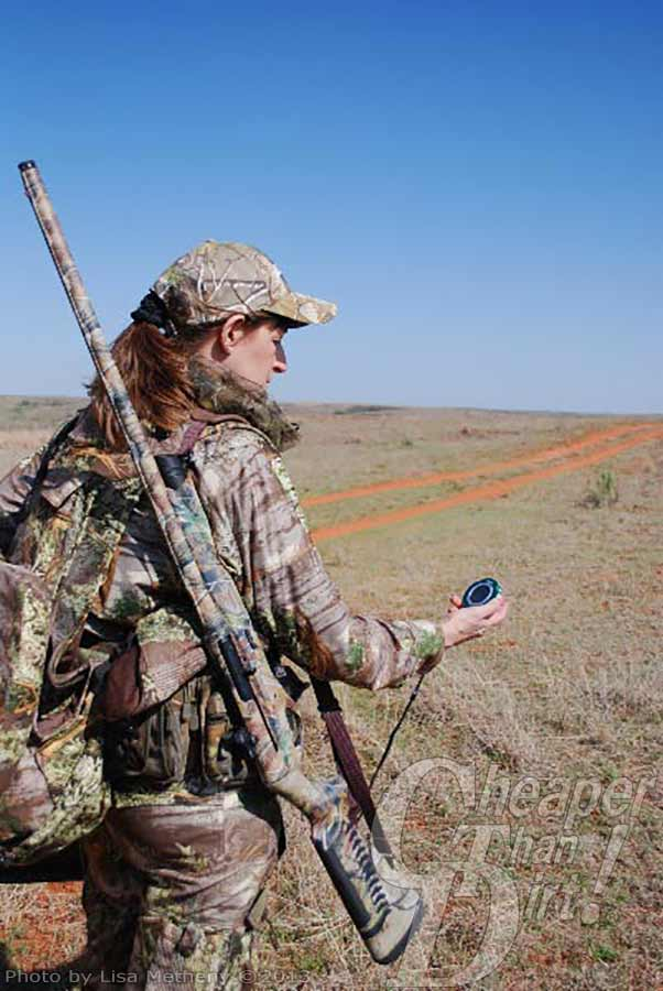 Huntress with shotgun over her shoulder and GPS in hand.