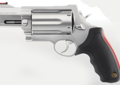 The Taurus Raging Judge, silver barrel pointed to the left and a black grip on a mottled light gray background