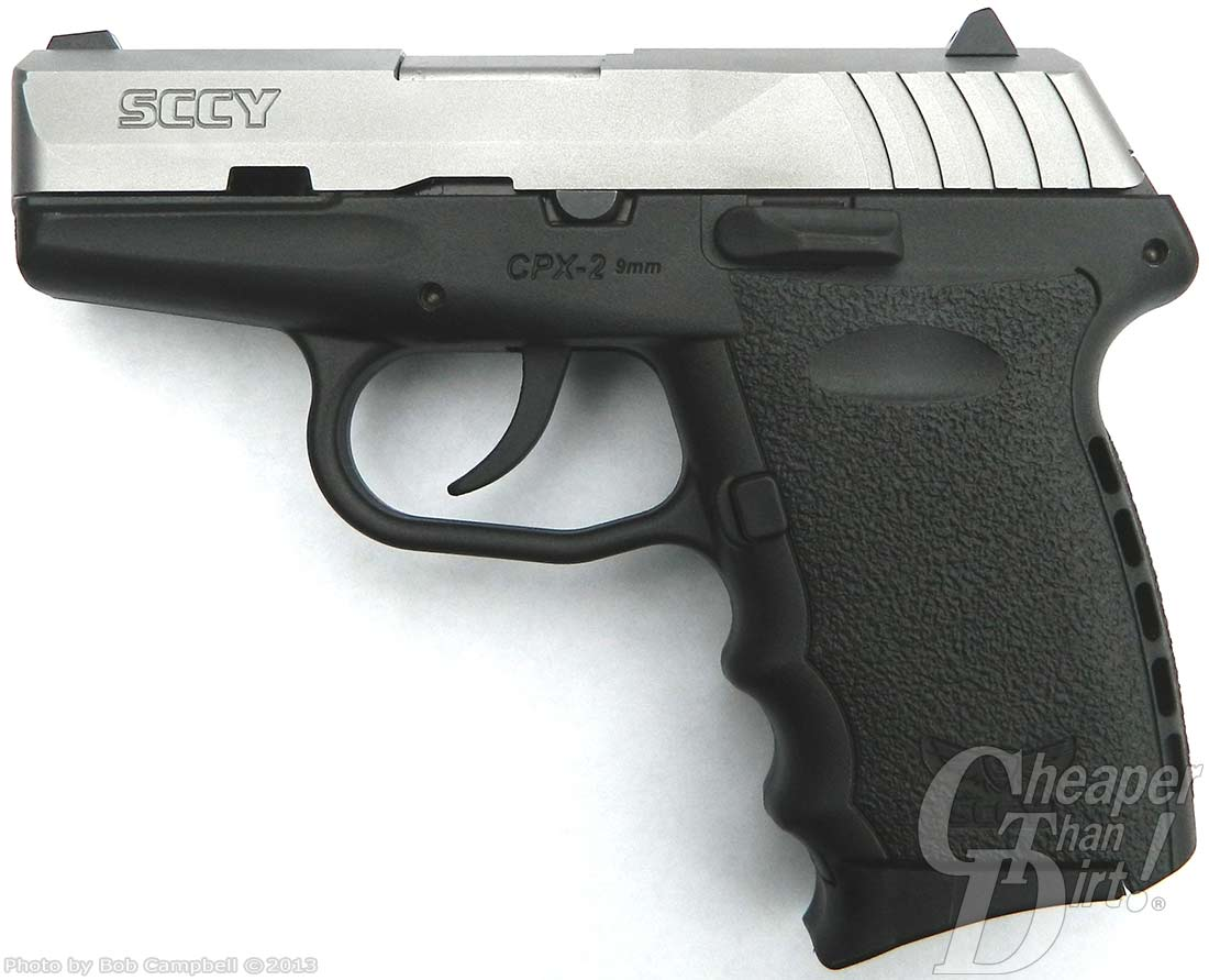 A black SCCY CPX 2 with a silver slide, muzzle pointed to the left side on a gradient gray and white background.