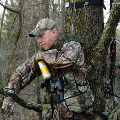 Hunter spraying scent elimination spray on clothing