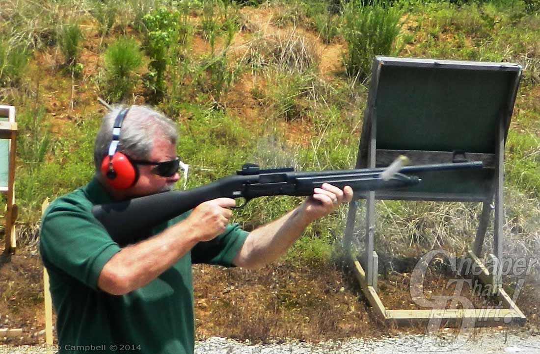Gray haired man in green shirt with red ear protection and safety glasses shoots a Raptor barrel facing the right, against a grassy background.