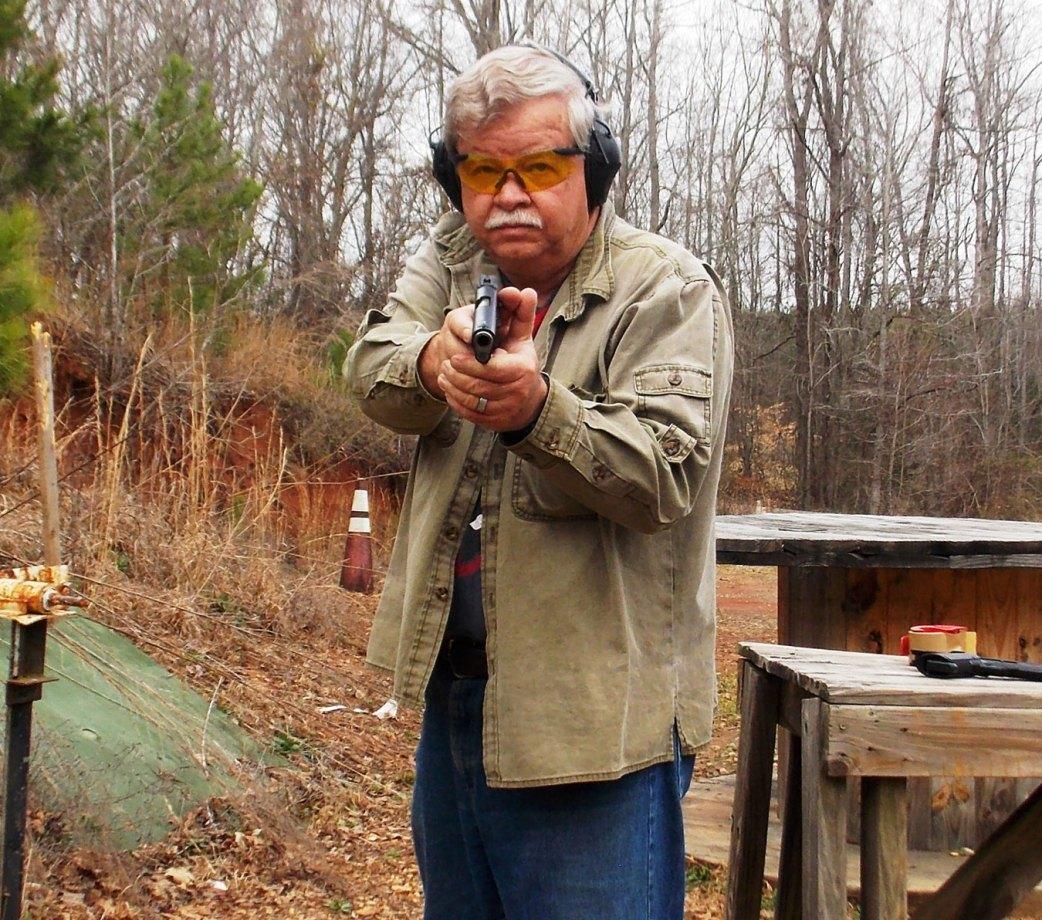 Bob Campbell pointing a pistol at the camera