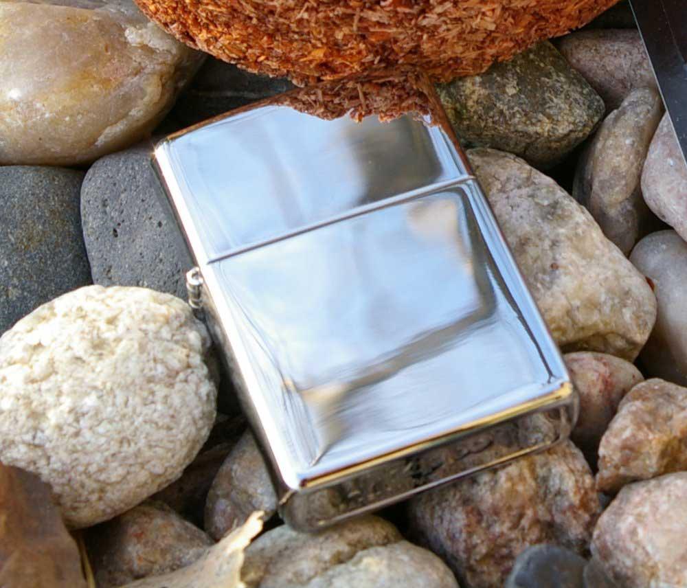 Shiny silver Zippo lighter on bed of rocks