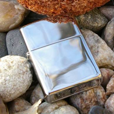 Shiny silver Zippo lighter on bed of rocks