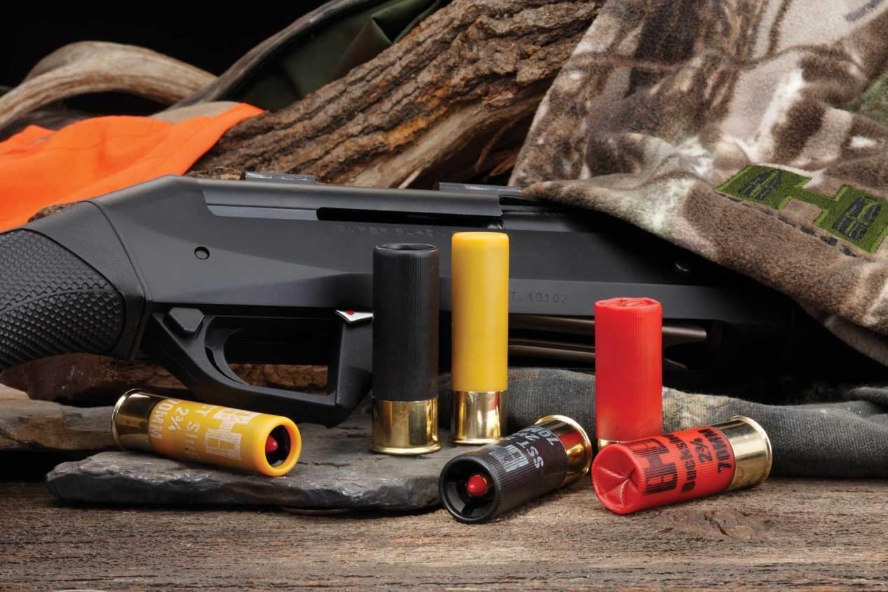 Assortment of 12 gauge shotguns shells with a shotgun and camo clothing