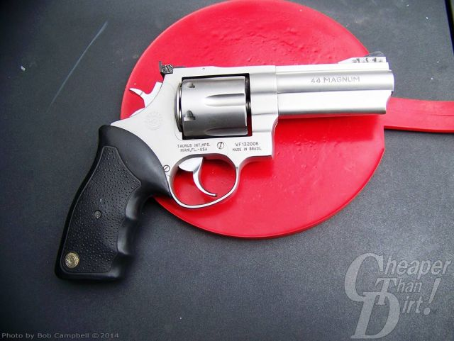 Taurus .44 Magnum, barrel pointed to the right, with a black grip on a dark-to-light gray background centered on a bright red shape.