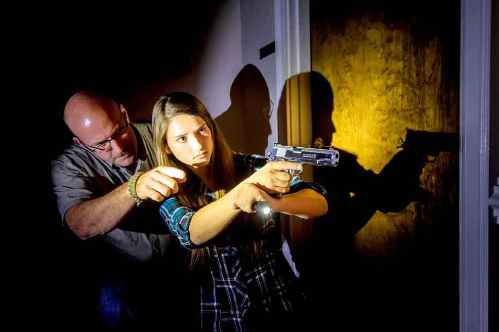 Woman shooting handgun with instructor
