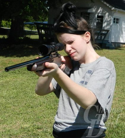 A young, dark haired boy shoots a black .223