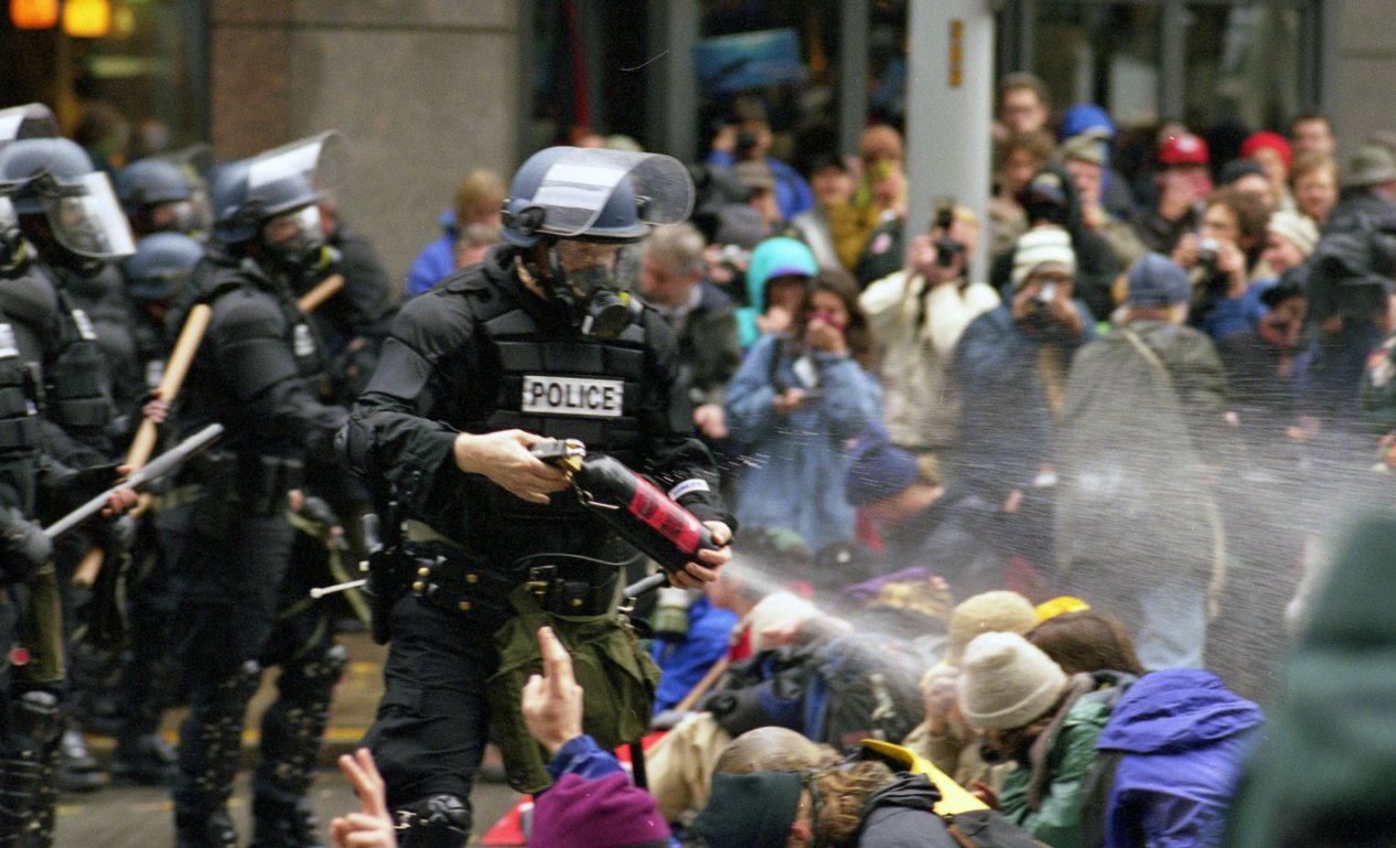 Picture shows a police spraying tear gas on protestors