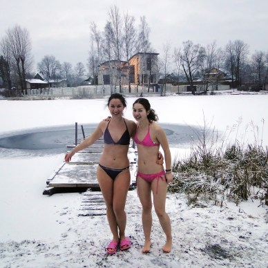 Picture show two young women standing in the snow by a pond with bikinis on.