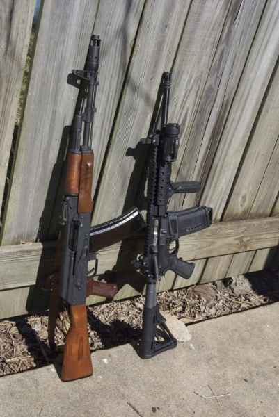 AR-15 AK47 leaning against a barnwood fence