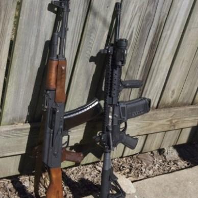 AR-15 AK47 leaning against a barnwood fence